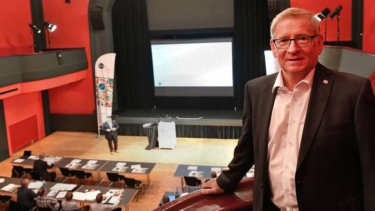 In den letzten 13 Jahren sein Arbeitsplatz: Geschäftsführer Herbert Schibler posiert auf dem Balkon des Theatersaals. Im Hintergrund läuft ein Firmenseminar.