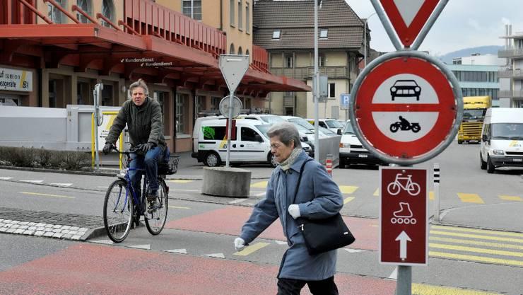 Verkehrssituation Hintere Bahnhofstrasse Aarau, 4. Maerz 2010. Ein Fussg?ngerstreifen und ein roter Radstreifen ohne Vortritt f?hrt ueber die Strasse. Velofahrer Fussgaenger.