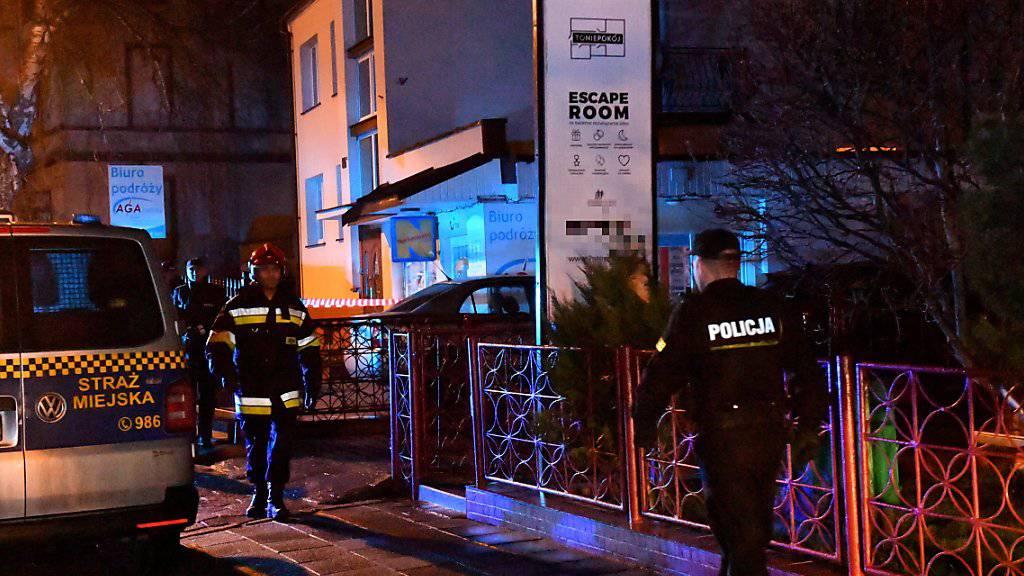 Polnische Polizisten riegeln das Gelände rund um die Freizeiteinrichtung mit dem vom Brand betroffenen «Escape Room» in Koszalin ab.