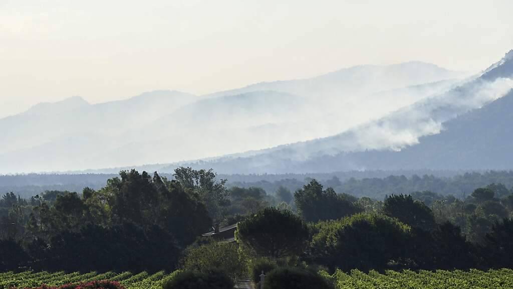 Rauch steigt über dem Wald auf. In Südfrankreich hat die Feuerwehr mit einem massiven Aufgebot in der Nacht zum Dienstag den Kampf gegen mehrere große Waldbrände fortgesetzt. Frankreichs Innenminister Gérald Darmanin sprach auf Twitter seine Unterstützung für die 650 Feuerwehrleute im Einsatz aus. Foto: Nicolas Tucat/AFP/dpa