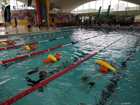 Die Athleten schwimmen mit dem Tube (gelbes Hilfsmittel) und können so im Ernstfall eine Person retten.