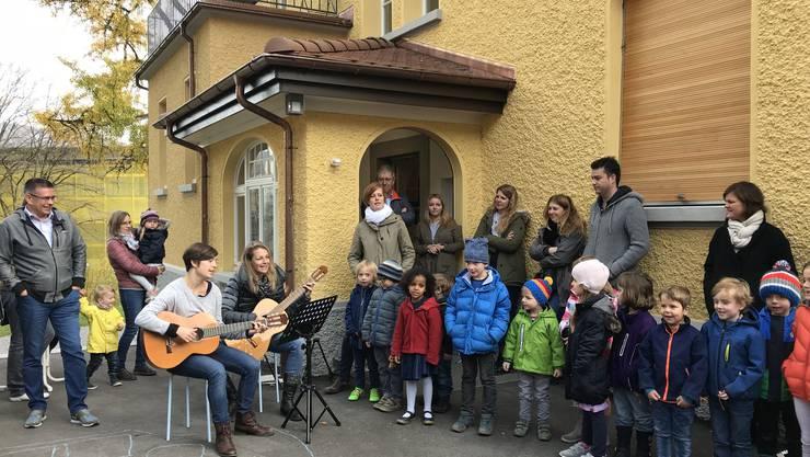 Kinder besingen zur Eröffnung ihr neues Gebäude. Links Vizeammann Markus Schneider und die Kindergärtnerinnen Claudia Zimmermann und Gaby Costoglus (mit Gitarre).