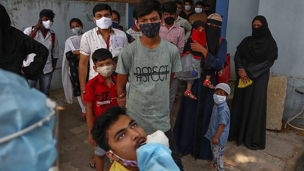 Ein Mitarbeiter des Gesundheitswesens in Indien nimmt eine Nasenabstrichprobe eines Mannes für einen Coronatest. Foto: Mahesh Kumar A./AP/dpa