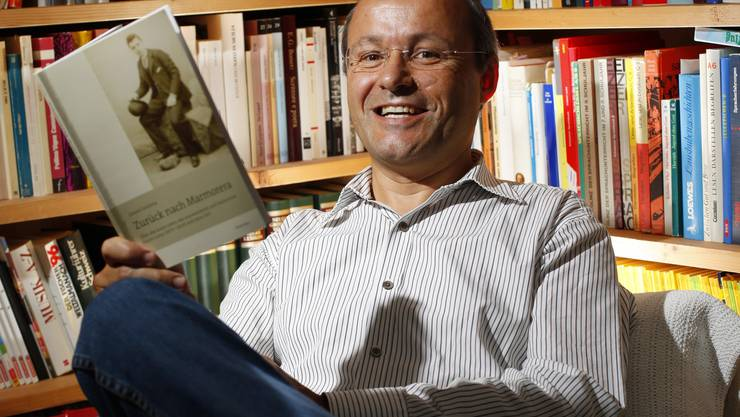 Lehrer und Schriftsteller Linard Candreia mit seinem neuesten Buch «Zurück nach Marmorera» über den Auswanderer Flurin Lozza. (Andreas Frossard)