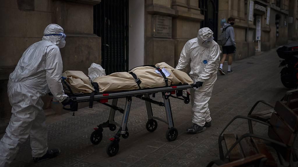 Leichenbestatter transportieren den Leichnam eines älteren Menschen, der in einem Pflegeheim an Covid-19 gestorben ist.