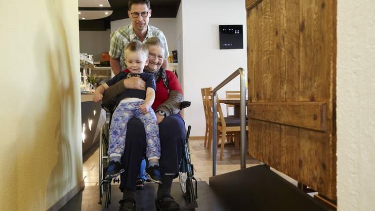 Erik (3) hat Dora zum Essen abgeholt. Gemeinsam werden sie im Rollstuhl von Papillon-Gründer Lukas Herren durch die Gänge geschoben.