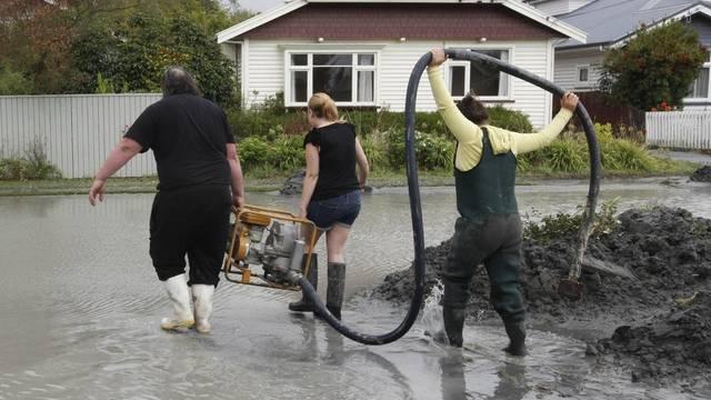 In einem Vorort Christchurchs: Anwohner tragen eine Wasserpumpe zu einem Haus