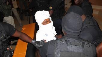Der frühere Diktator Tschads, Hissène Habré (in weiss), umringt von Sicherheitsmännern im Gericht