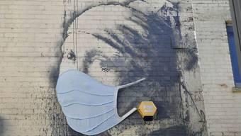 """Banksys Streetart-Version von Vermeers """"Mädchen mit dem Perlenohrring"""" wurde aus Gründen der Aktualität mit einem Mundschutz versehen. Indessen haben Forscher das Originalbild untersucht und überraschende Entdeckungen gemacht. (Archivbild 22.4.)"""