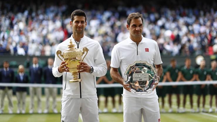 Novak Djokovic mit dem Pokal und Roger Federer mit dem Teller nach der Siegerehrung.