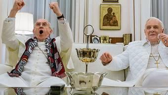 Bregoglio (J. Pryce links) und Ratzinger (A. Hopkins) schauen gemeinsam Fussball.