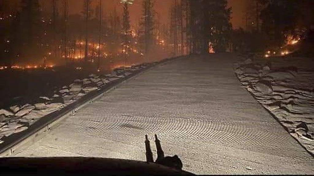 HANDOUT - Blick über einen Waldbrand in einem Nationalpark in der Sierra Nevada aus einem Transporthubschrauber der Kalifornischen Nationalgarde «California National Guard». Mehr als 200 von einem Waldbrand eingeschlossene Menschen sind in Kalifornien in Sicherheit gebracht worden. Foto: -/California National Guard/AP/dpa - ACHTUNG: Nur zur redaktionellen Verwendung und nur mit vollständiger Nennung des vorstehenden Credits