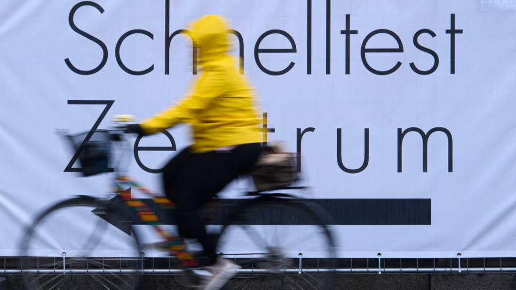 dpatopbilder - Eine Fahrradfahrerin fährt an einem Banner mit der Aufschrift «Schnelltest Zentrum» vorbei. Foto: Robert Michael/dpa-Zentralbild/dpa