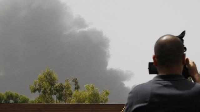 Ein Kameramann filmt Rauchwolken über der libyschen Hauptstadt