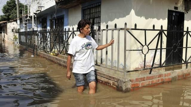 Eine Kolumbianerin schreitet in Juanchito durch kniehohes Wasser