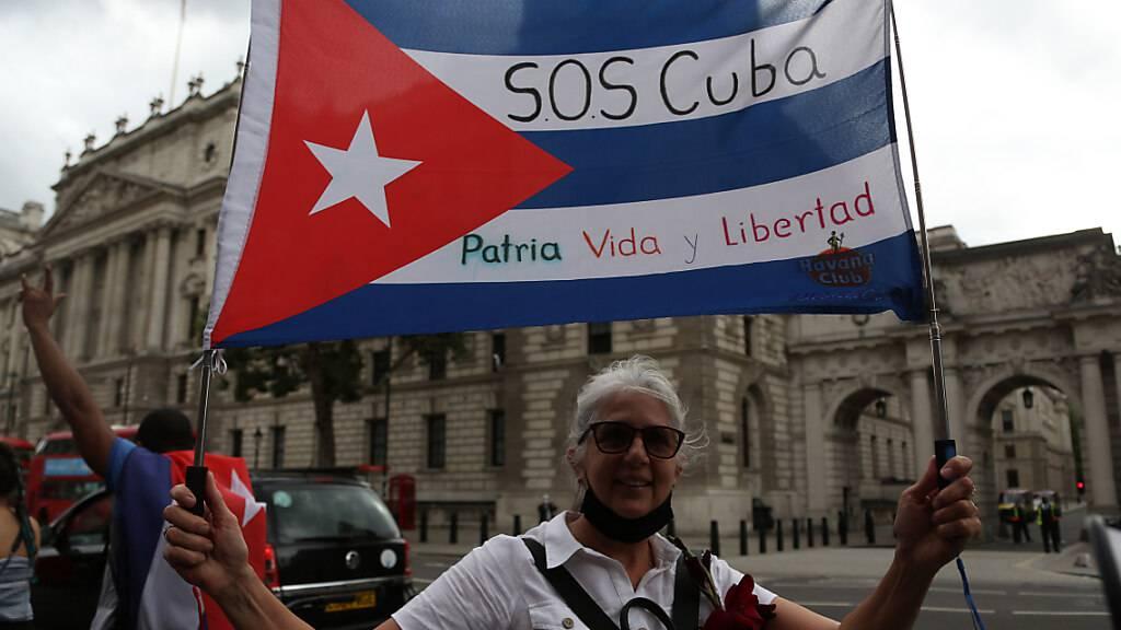 Ein Mann hält eine Fahne in den Farben der kubanischen Nationalflagge mit der Aufschrift «S.O.S Cuba, Patria Vida y Libertad» (S.O.S Kuba, Vaterland, Leben und Freiheit) bei einem Protest im Zentrum Londons. Menschen protestierten, um ihre Solidarität mit den Regierungsgegnern in Kuba zu bekunden. Foto: Tayfun Salci/ZUMA Press Wire/dpa