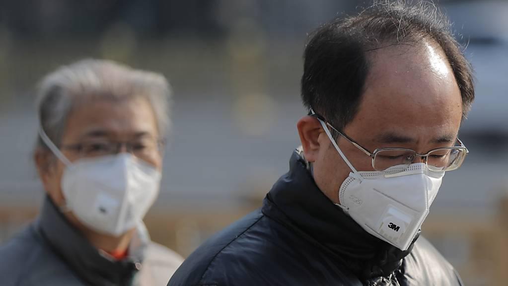 In Frankreich noch kein übliches Bild: Menschen mit Atemschutz. Aber in Peking umso mehr, wie diese beiden Männer.