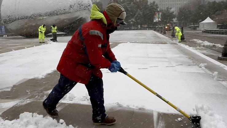 Strassenarbeiter beim Schneeschaufeln in Chicago am Montagmorgen. Dem heftigen Schneefall fielen am internationalen Flughafen hunderte Flüge zum Opfer.