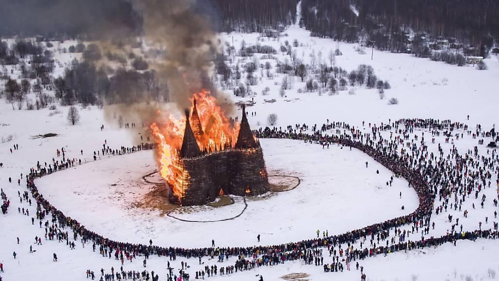 dpatopbilder - Menschen beobachten die Verbrennung einer schlossförmigen Holzkonstruktion als Teil der Feierlichkeiten zum Masleniza-Fest im Nikola-Lenivets-Kunstpark. Foto: Dmitry Serebryakov/AP/dpa