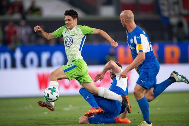 Wolfsburgs Josip Brekalo (l) spielt gegen Kiels Dominic Peitz (M) und Patrick Hermann.
