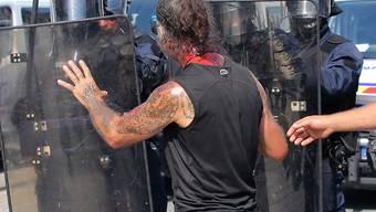 Unruhen nach dem Tod eines Mannes: Ein Demonstrant mit Blut am Hals konfrontiert Polizisten in Nantes.