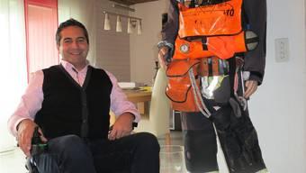 Mike Hunziker in seiner Wohnung neben «Miggu», der seine allererste Feuerwehrausrüstung trägt.
