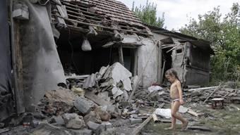 Ein Mädchen vor seinem zerstörten Zuhause in der Region Donezk.