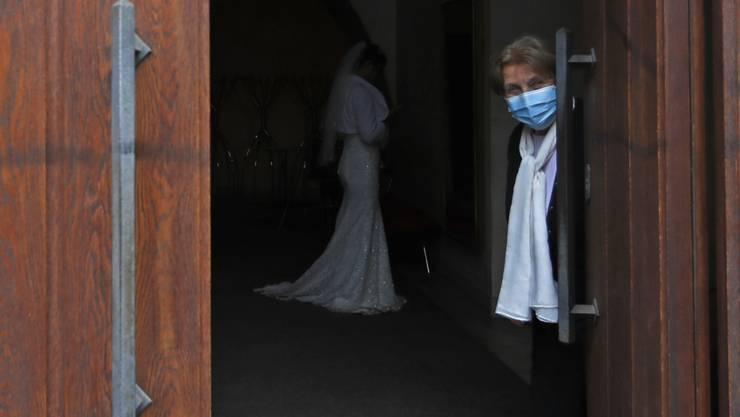 Eine Frau, die eine Mund-Nasen-Bedeckung trägt, hält eine Tür für eine Hochzeit in Prag geöffnet. Foto: Petr David Josek/AP/dpa