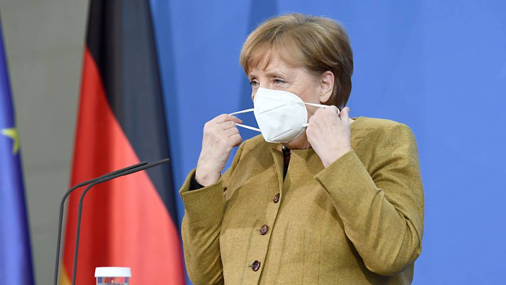 Bundeskanzlerin Angela Merkel (CDU) zieht sich vor einer Pressekonferenz im Anschluss an den virtuellen G7-Gipfel im Februar 2021 eine Maske an.