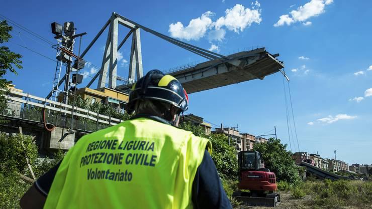 Ein Arbeiter inspiziert die Umgebung um die eingestürzte Morandi-Brücke.