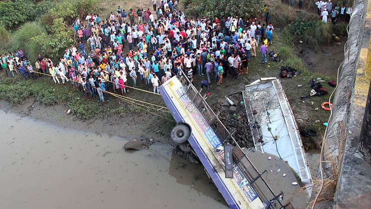 Schaulustige und Helfer versammeln sich um die Überreste des von einer Brücke gestürzten Busses.