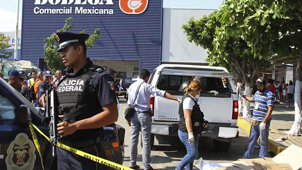Schwerbewaffnete Polizisten sichern den Markt in Acapulco, auf dem sechs Menschen erschossen wurden.