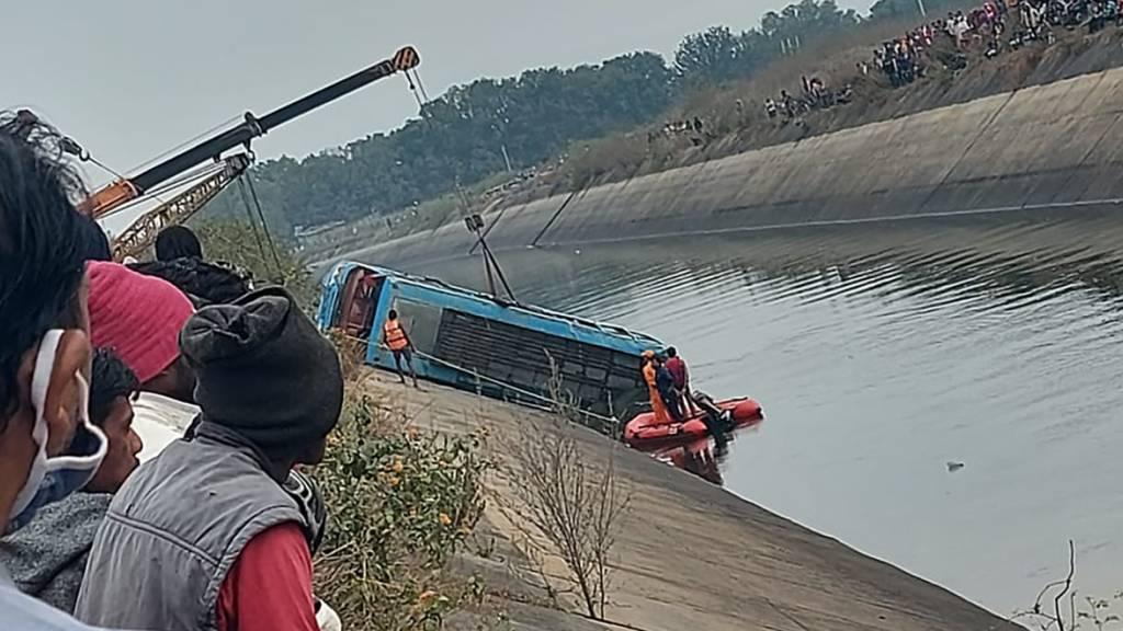 HANDOUT - Ein Bus, der in einen Kanal gestürzt ist, wird im Bezirk Sidhi im zentralindischen Bundesstaat Madhya Pradesh geborgen. Foto: Madhya Pradesh District Public Relation Office Sidhi/AP/dpa - ACHTUNG: Nur zur redaktionellen Verwendung und nur mit vollständiger Nennung des vorstehenden Credits