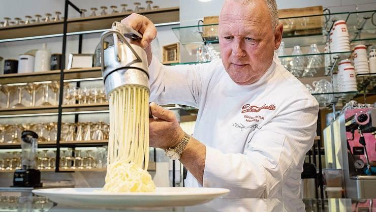 Spaghetti-Eis-Erfinder Dario Fontanella drückt in seinem Eiscafé Vanilleglace durch eine Spätzlepresse.