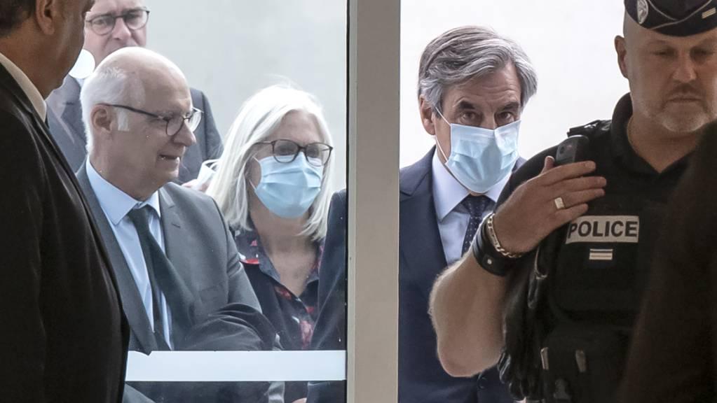Francois Fillon (Mitte, r), ehemaliger Premierminister von Frankreich, und seine Frau Penelope (Mitte, l) beim Eintreffen im Gerichtsgebäude. Foto: Michel Euler/AP/dpa