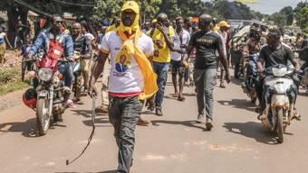 Anhänger der Regierungspartei «Partei des Volkes von Guinea» demonstrieren gegen die Opposition. Foto: Sadak Souici/AP/dpa