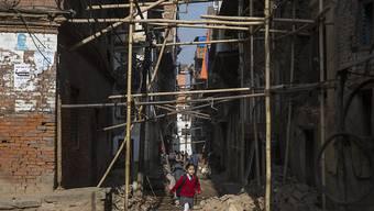 Kind in Kathmandu auf seinem Schulweg, der unter stützenden Verstrebungen hindurchführt (Archiv)