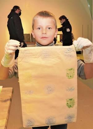 Noel zeigt sein «Turnsäcklein». Der viereinhalbjährige Gino streicht Farbe auf dem Schwamm. Joshua (10) hat sich für einen grossen Druckstock entschieden.