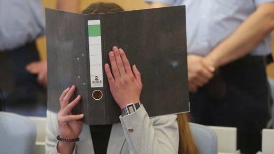 Sarah O. versteckt ihr Gesicht hinter einem Aktenordner.