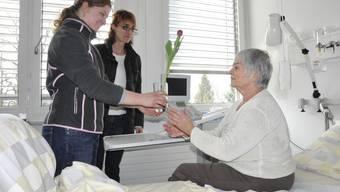 Florence Schacher und Flurina Hoffmann (v. l.) vom SRK Aargau schenken einer Patientin am «Tag der Kranken» im Kantonsspital Aarau eine Tulpe im Wasserglas.