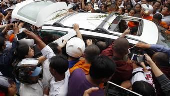 Die Leiche von  Kem Ley wird in einem geöffneten Kombi zum Verbrennungsort gebracht.
