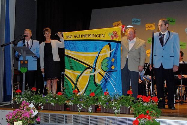 Die neue Vereinsfahne der Musikgesellschaft Schneisingen ist entrollt.  Von links am Rednerpult Hanspeter Bräm, Fahnengotte Monika Madl, Fahnengötti Franz Schmid und Fähnrich Josef Lehmann.