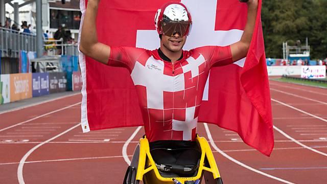 Marcel Hug jubelt mit Fahne über seine Goldmedaille.
