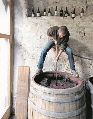 Winzer Markus Ruch rührt die Pinot-noir-Maische im Gärfass regelmässig von Hand um.