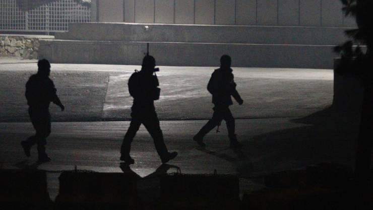 Afghanische Sicherheitskräfte nähern sich dem von Terroristen besetzten Hotel in Kabul.