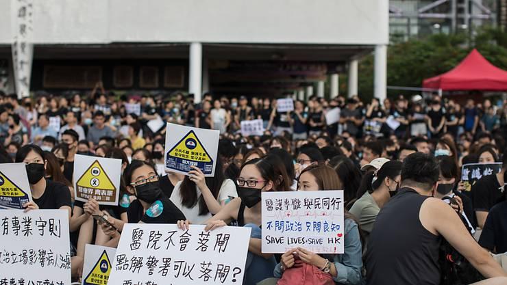 Mit Gesichtsmaske an der Demonstration: Staatsbedienstete auf der Strasse in Hongkong.