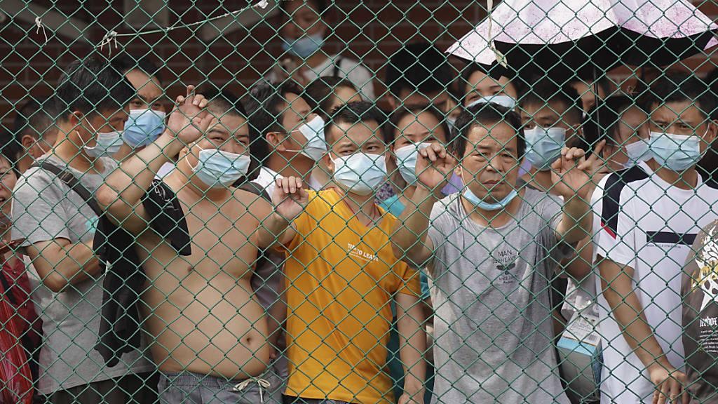 Anwohner warten hinter einem Zaun auf ihren Corona-Test. Nach einem Anstieg der Corona-Infektionen wurde ein Teil der südchinesischen Stadt Guangzhou gesperrt und die Bewohner wurden dazu aufgefordert, zu Hause zu bleiben, um auf das Coronavirus getestet zu werden. Foto: Uncredited/AP/dpa Foto: Uncredited/AP/dpa