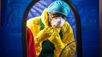 Ein Pfleger zieht sich in Sierra Leone Ebola-Schutzkleidung an