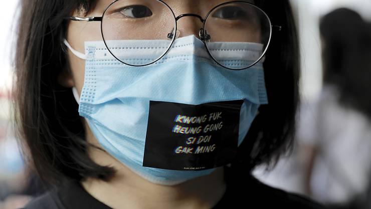 """Eine Frau trägt während einer Anti-Regierungs-Demonstration in Hongkong eine Maske mit der Aufschrift """"Fügt Öl hinzu, Leute aus Hongkong""""."""