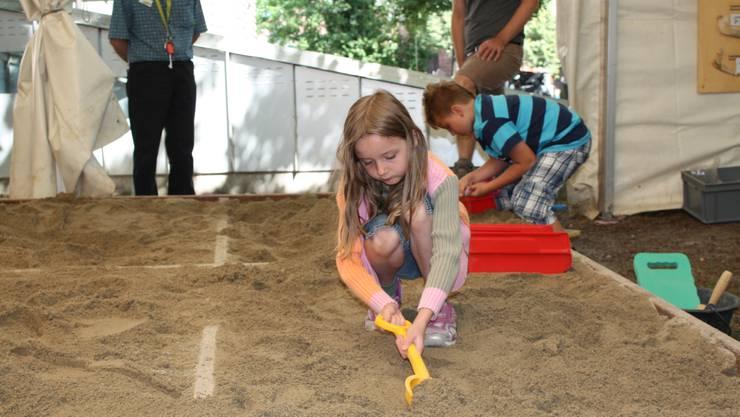 Konzentriert und vorsichtig sucht das Mädchen im Sand nach vergrabenen Gegenständen, die es nachher säubern und dokumentieren wird.
